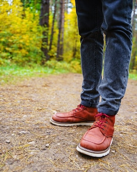 A man in red leather boots walks in the amazing autumn forest. footwear close up with copy spase. travel concept.
