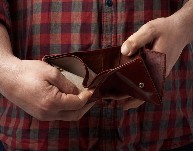 Man in a red plaid shirt holds an empty leather brown wallet