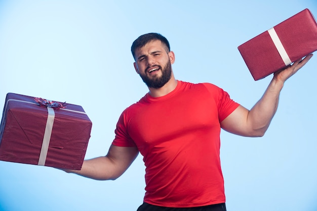 Man in red shirt holding gift boxes in both hands.