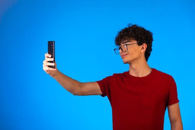 Uomo in camicia rossa che prende selfie o fa una telefonata e si diverte.