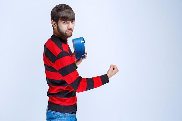 Uomo in camicia a righe rosse che tiene una scatola regalo blu a forma di cuore e mostra il pugno.