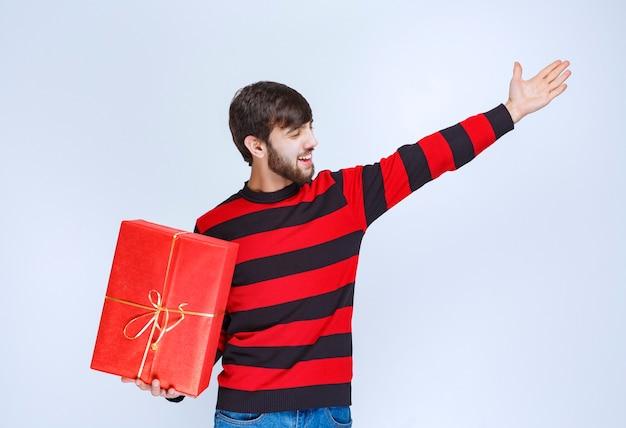 Uomo in camicia a righe rosse che tiene in mano una confezione regalo rossa e chiede a qualcuno di consegnarlo.