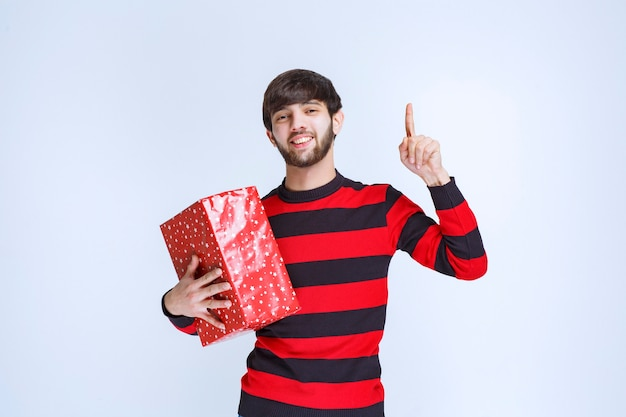 Man in red striped shirt holding a red gift box and calling for someone to deliver it.
