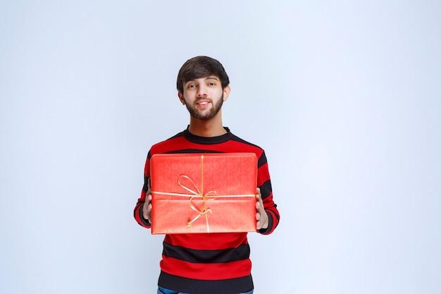 Uomo in camicia a righe rosse che tiene in mano una confezione regalo rossa, che la consegna e la presenta al cliente o alla sua ragazza.