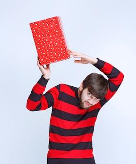Uomo in camicia a righe rosse con in mano una scatola regalo rossa, che la consegna e la presenta