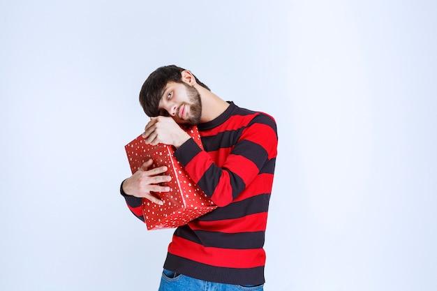 Uomo in camicia a righe rosse che tiene in mano una scatola regalo rossa e lo abbraccia stretto e non vuole condividerlo con nessuno.