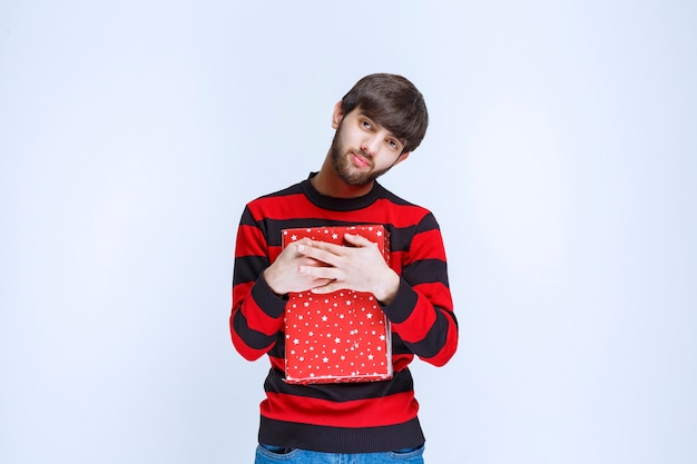Man in red striped shirt holding a red gift box and hugging it tight and do not want to share with anybody.