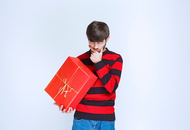 L'uomo in camicia a righe rosse tiene in mano una confezione regalo rossa e sembra confuso e pensieroso.