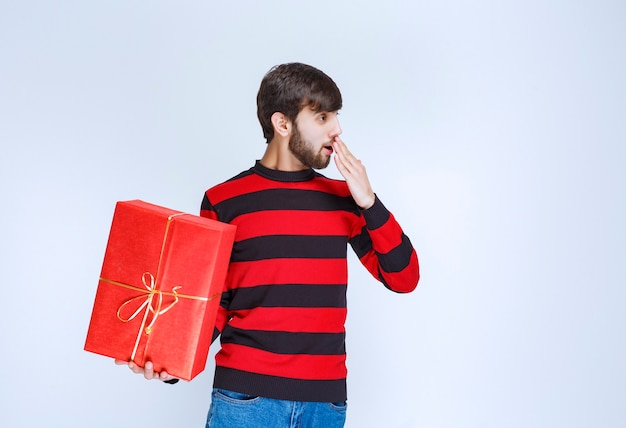 L'uomo in camicia a righe rosse con in mano una confezione regalo rossa sembra stanco e assonnato.