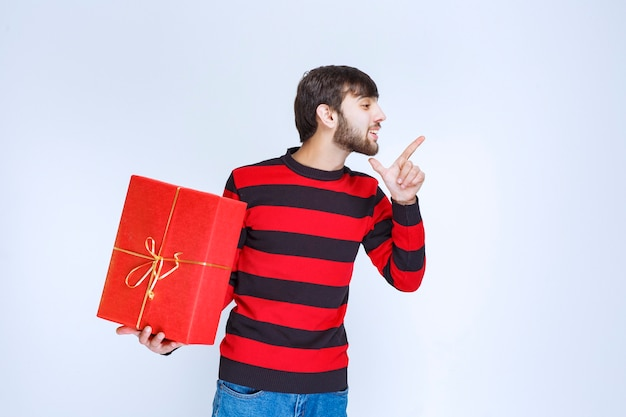 Uomo in camicia a righe rosse che tiene una confezione regalo rossa e la promuove.