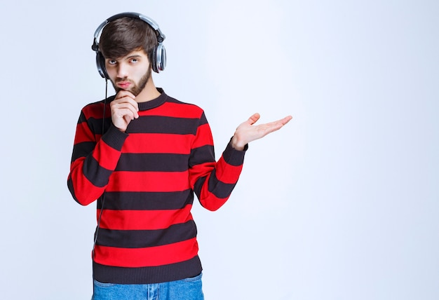 Man in red striped shirt listening to headphones and looks confused and thoughtful.