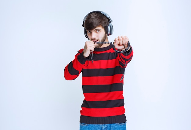Uomo in camicia a righe rossa che ascolta le cuffie e imposta la musica dalla sua playlist sullo smartphone.