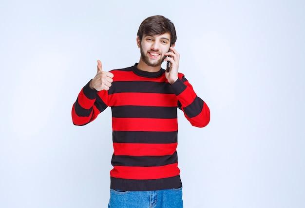 Uomo in camicia a righe rosse che parla al telefono e mostra il pollice mentre sente buone notizie.