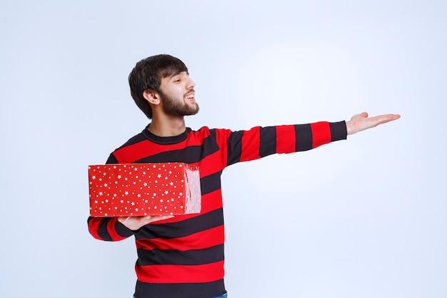 Uomo in camicia a righe rosse con una confezione regalo rossa e che chiama qualcuno per presentarlo.