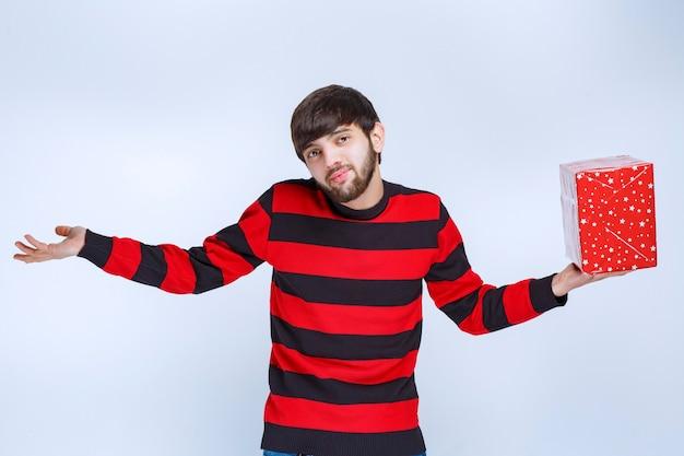 L'uomo in camicia a righe rosse con una confezione regalo rossa sembra confuso e pensieroso.