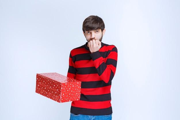 L'uomo in camicia a righe rosse con una confezione regalo rossa sembra spaventato e spaventato.