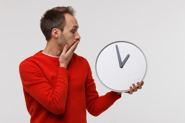 Man in red sweater holding big round clock, in shock covers his mouth with his hand. lack of time