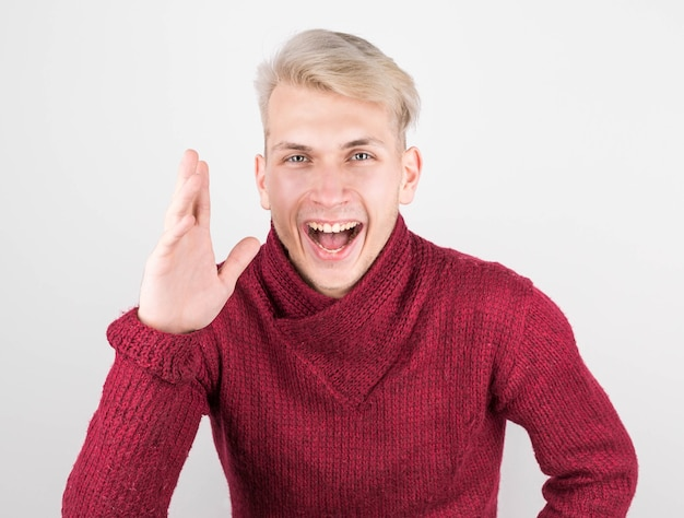 Man in a red sweater with a beard laughs holding his stomach
