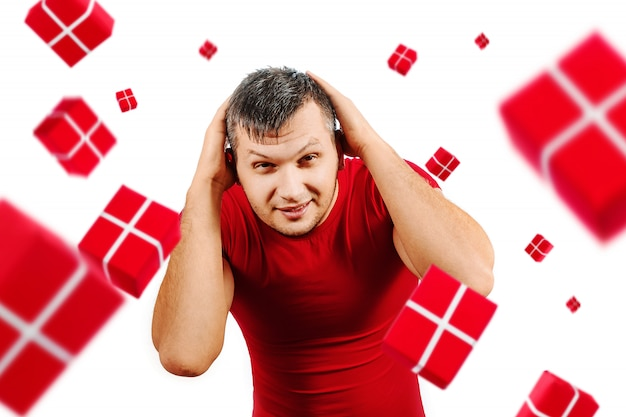 A man in a red t-shirt is hiding from gifts falling from above on white