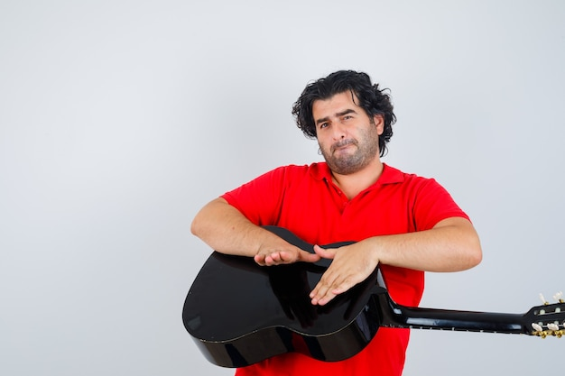 Man in red t-shirt knocking on guitar and looking happy
