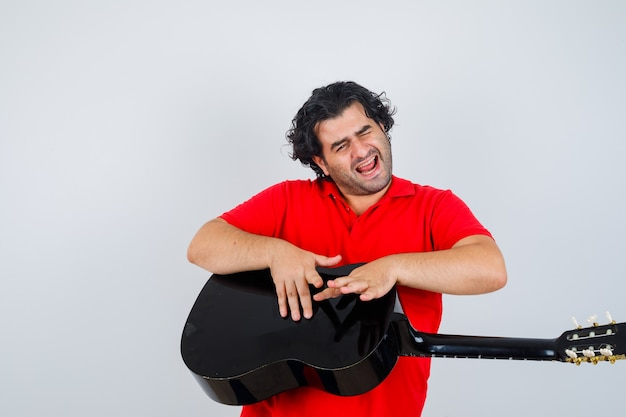 Man in red t-shirt knocking on guitar and looking jolly