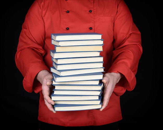 Man in red uniform holds a stack of books