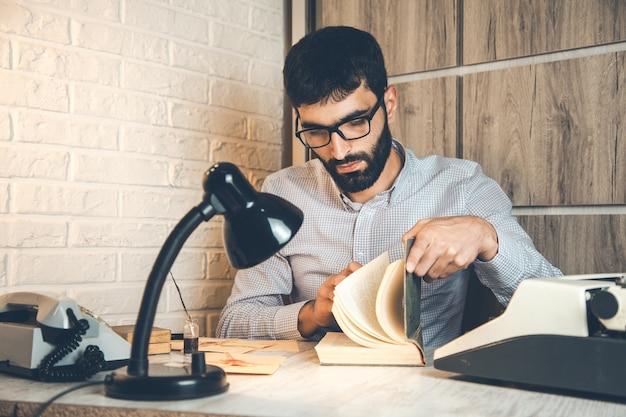 Человек reding книга и пишущая машинка на столе