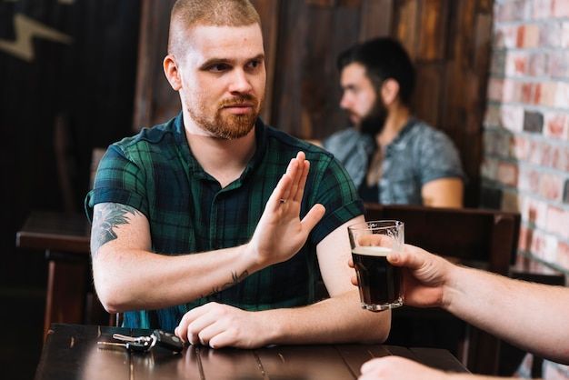 Man refusing alcoholic drink offered by his friend in bar