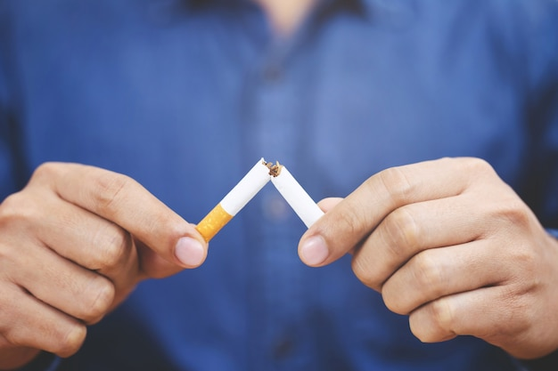 禁煙と健康的なライフスタイルのためのタバコの概念を拒否する男性。または禁煙キャンペーンの概念。