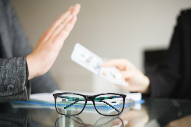 Man rejecting money and glasses over the glass table
