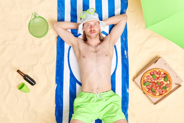 Man relaxes at beach lies on blue striped towel eats pizza drinks beer wears panama and shorts sunbathes in sun enjoys vacations
