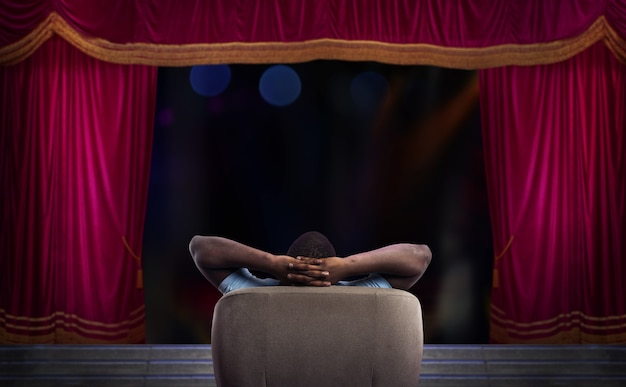 Man relaxing on a armchair and watches a show in a theatre
