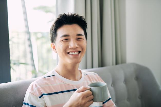 소파에서 집에서 휴식을 취하고 커피를 마시는 남자, 그는 웃고 컵을 들고 있다