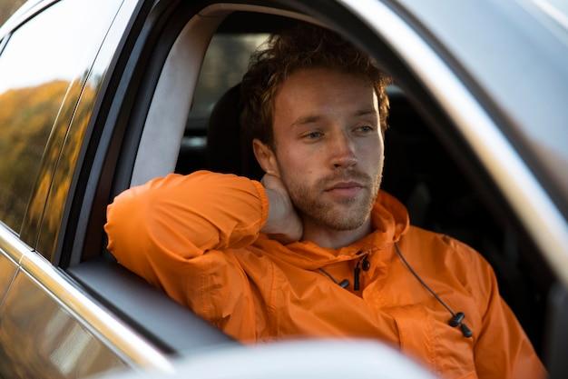 Uomo che si distende in macchina durante un viaggio su strada