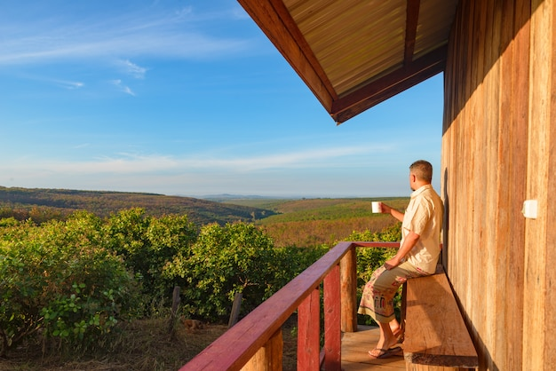 Man relaxing in the countryside, sitting in balcony wooden cabin, drinking coffee, watching landscape at sunrise, traveling wanderlust, outdoors activities.
