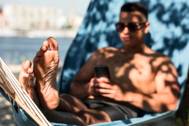 Man relaxing in hammock while at the beach