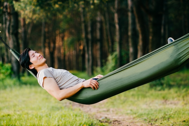 Человек отдыхает в гамаке в лесу летом