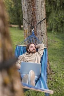 Человек отдыхает в гамаке во время работы на ноутбуке