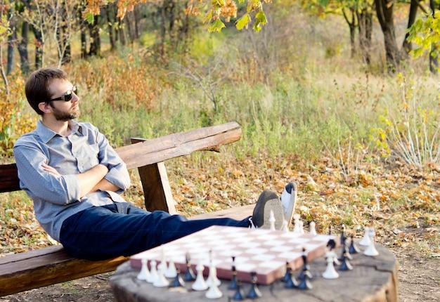 체스 상대를 기다리는 나무 그루터기에 자신의 발을 가진 삼림 지대에있는 소박한 나무 벤치에서 편안한 남자 프리미엄 사진
