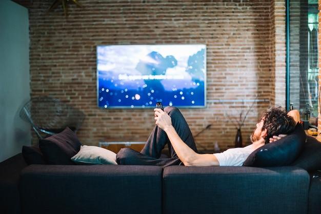 Человек, расслабляющий на диване у себя дома
