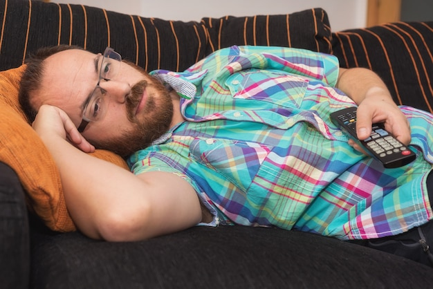 Man relaxing in sofa with remote control watching tv.