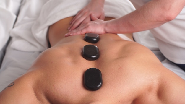 Man relaxing in wellness spa center with hot stones on body.