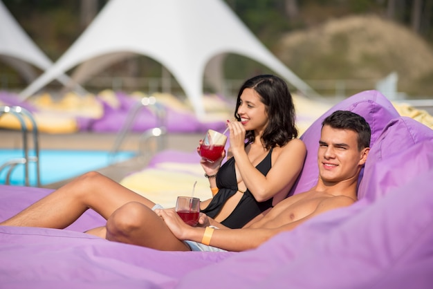 Man relaxing with girlfriend near swimming pool
