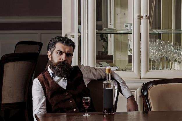 병 및 유리 알코올 및 전채와 함께 테이블에 앉아 수염을 가진 레스토랑 힙 스터에서 와인과 함께 편안한 남자