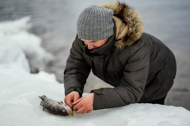 Человек выпускает рыбу из удочки