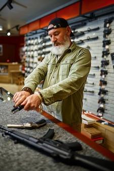 男は銃店のカウンターで拳銃をリロードします