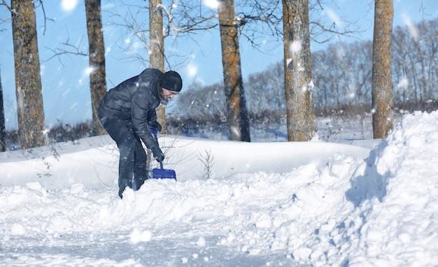 男は雪の降る冬に道路からシャベルで除雪