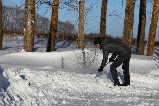 男は冬の日に道路からシャベルで除雪