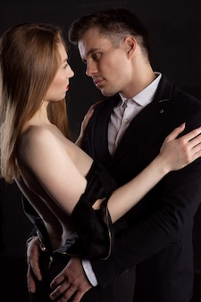A man removes a dress from a sexy woman who gently embraces him at the moment of foreplay.