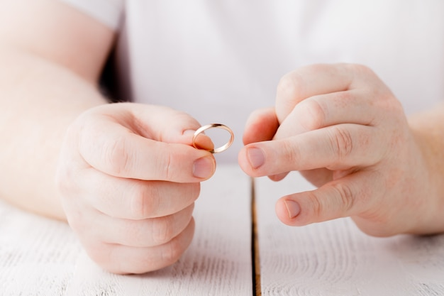 Man removes a gold wedding ring from his finger. concept of family quarrel, divorce or betrayal